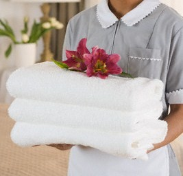 Maid Holding Fresh Towels with Flower Blossoms --- Image by © Corbis